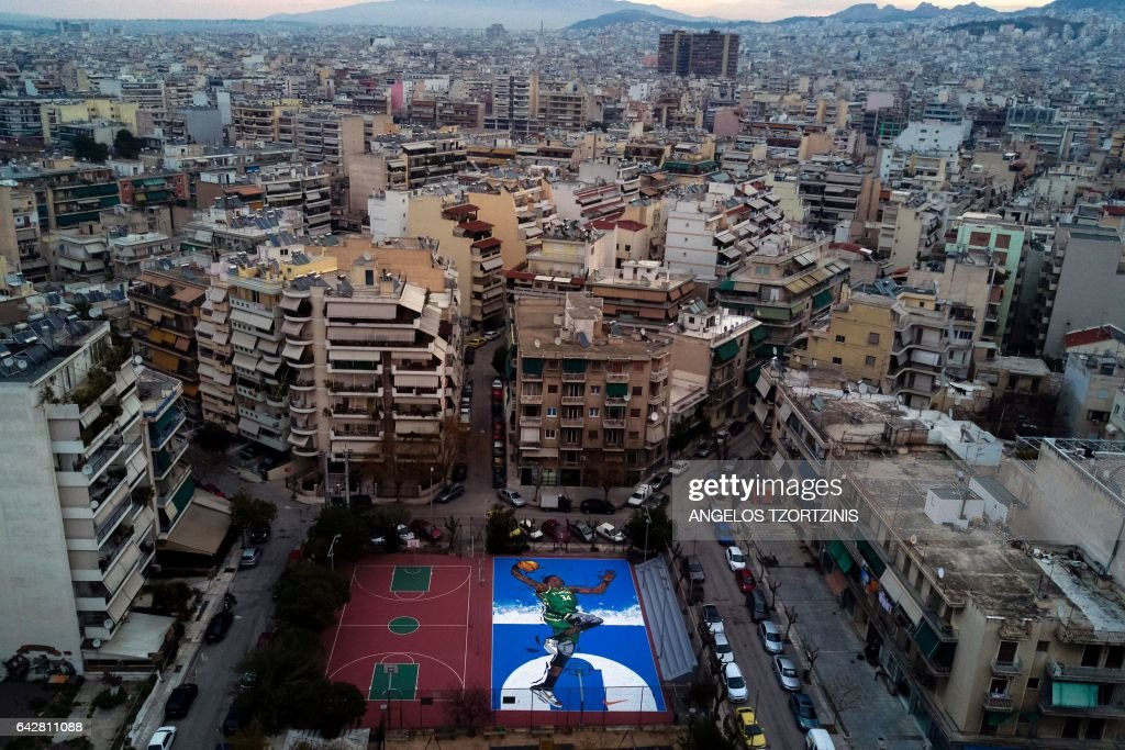 An aerial picture taken on February 19, 2017, shows an artwork by street artist Same84 depicting Milwaukee Bucks' Greek basketball player Giannis Antetokounmpo on a basketball court in Athens. Greek NBA player Giannis Antetokounmpo began playing basketball in an open field in Athens neighbourhood of Sepolia. He was drafted number 15 in the NBA in 2013 and now participates in his first All Star Game. / AFP / Angelos TZORTZINIS / RESTRICTED