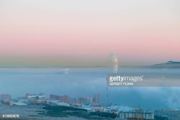 An aerial picture taken on January 4, 2018 shows a photochemical smog over the city of Krasnoyarsk. - Weary of local officials dismissing the deadly...