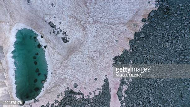 An aerial picture taken on July 3, 2020 above the Presena glacier near Pellizzano, shows pink colored snow, supposedly due to the presence of...