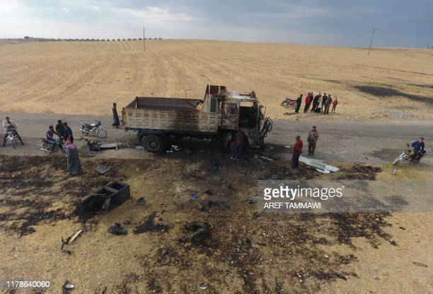 An areal picture taken on October 28 shows Syriacn locals near a destroyed truck at the spot where Abu Hassan alMuhajir the Islamic State group's...