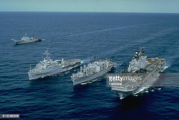 An aerial port bow view of the amphibious assault ship USS Saipan the combat stores ship USS Concord the amphibious transport dock USS Nashville and...