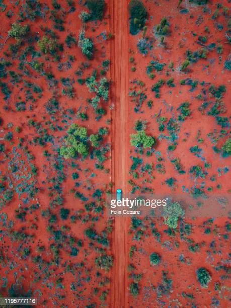 an aerial shot of a car driving on the red centre roads in the australian outback - darwin australia stock pictures, royalty-free photos & images
