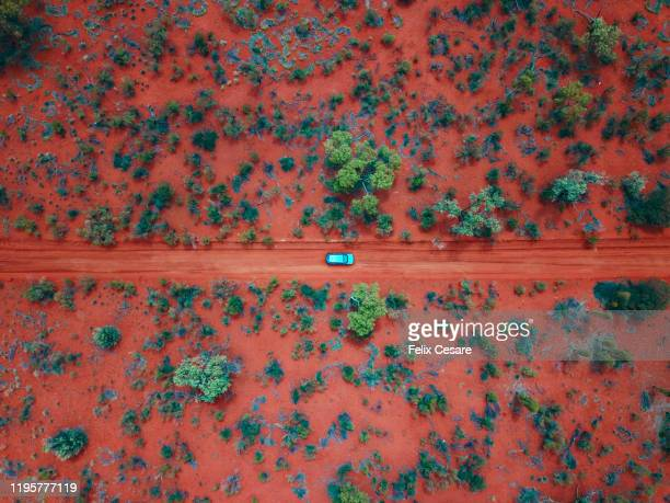 an aerial shot of a car driving on the red centre roads in the australian outback - australia fotografías e imágenes de stock