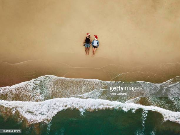 an aerial shot of a young couple sitting on the beach with a santa hat - beach christmas stock pictures, royalty-free photos & images