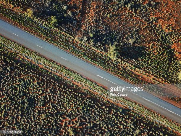 an aerial shot of the red centre roads in the australian outback - darwin australia stock pictures, royalty-free photos & images