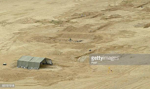 An aerial shot shows a forensic specialist walking near a mass grave discovered in alSamawa desert on April 25 2005 in Muthanna province 270km south...