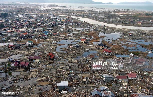 An aerial shot shows flattened houses near the sea coast of Banda Aceh 05 January 2005 US Secretary of State Colin Powell toured Indonesia's...