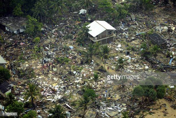 An aerial shot taken from a helicopter shows a house standing amid debris of houses destroyed by tsunamis in the Galle district in the southwestern...