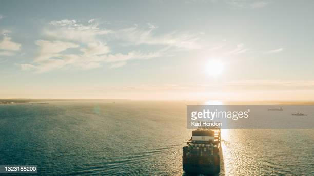 an aerial sunset view of a container ship on the solent sea, uk - stock photo - horizon over water stock pictures, royalty-free photos & images