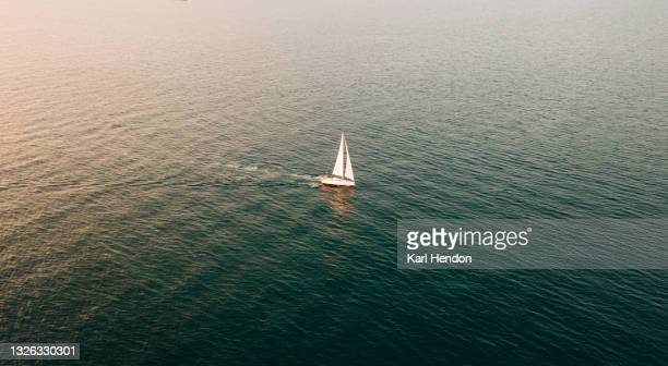 an aerial sunset view of a sailing boat on the solent - stock photo - yachting stock pictures, royalty-free photos & images