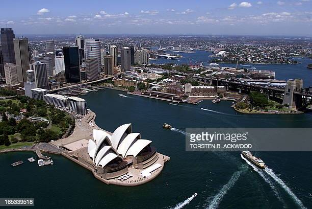 An aerial view 15 December 1999 shows ferries passing the Sydney Opera House which will be the venue for the triathlon during the Sydney 2000 Olympic...
