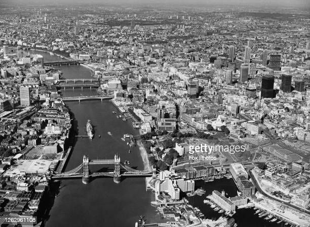 An aerial view along the River Thames in London with Tower Bridge in the foreground and the Tower of London to the right of it September 1974 St...