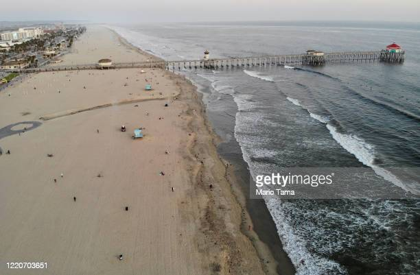 An aerial view as people gather on Huntington Beach which remains open amid the coronavirus pandemic at dusk on April 23 2020 in Huntington Beach...