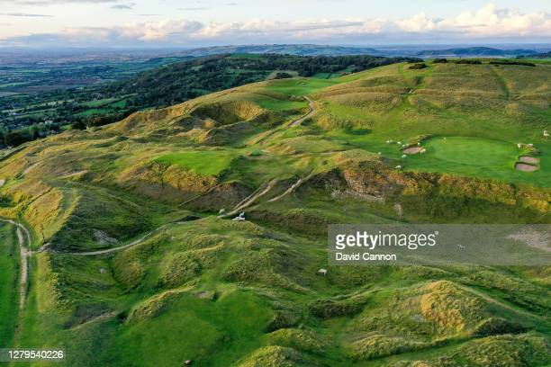 An aerial view as sheep graze on the course of the par 3, 15th hole and the par 3, 16th hole at Cleeve Hill Golf Club on October 06, 2020 in...