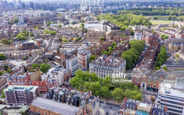 An aerial view by drone of Sloane Square showing London and the River Thames behind showing Peter Jones store and Sloane Square tube station on May...