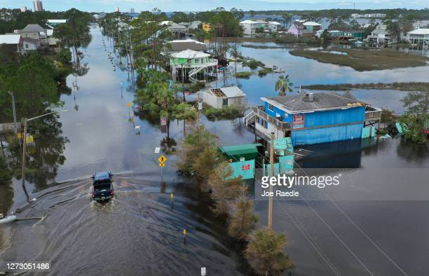 An aerial view from a drone shows a vehicle driving through a flooded street after Hurricane Sally passed through the area on September 17 2020 in...