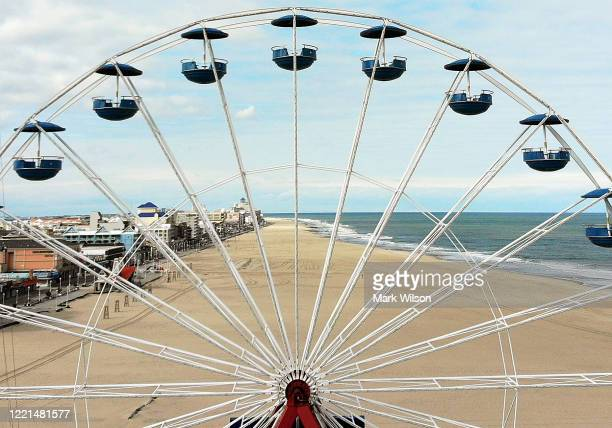 An aerial view from a drone shows an empty beach through a ferris wheel on April 27 2020 in Ocean City Maryland The beach and boardwalk were closed...