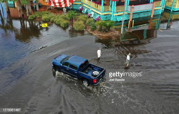 An aerial view from a drone shows people walking and a vehicle driving through a flooded street after Hurricane Sally passed through the area on...