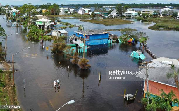 An aerial view from a drone shows people walking through a flooded street after Hurricane Sally passed through the area on September 17 2020 in Gulf...