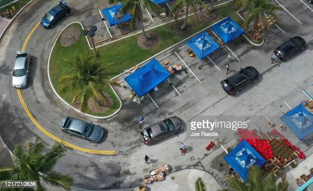 An aerial view from a drone shows vehicles passing though as they receive food provided by the food bank Feeding South Florida and being given away...