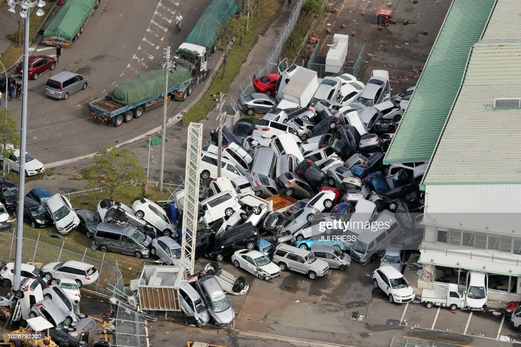 TOPSHOT - An aerial view from a Jiji Press helicopter shows vehicles piled in a heap due to strong winds in Kobe, Hyogo prefecture on September 5, 2018, after typhoon Jebi hit the west coast of Japan. - The toll in the most powerful typhoon to hit Japan in a quarter century rose on September 5 to nine, with thousands stranded at a major airport because of storm damage. (Photo by JIJI PRESS / JIJI PRESS / AFP) / Japan OUT