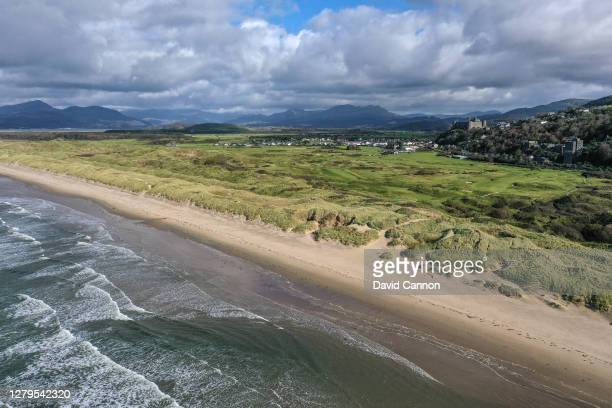 An aerial view from out to sea of the course looking back towards the clubhouse, Harlech Castle and the mountains of Snowdonia at Royal St Davids...
