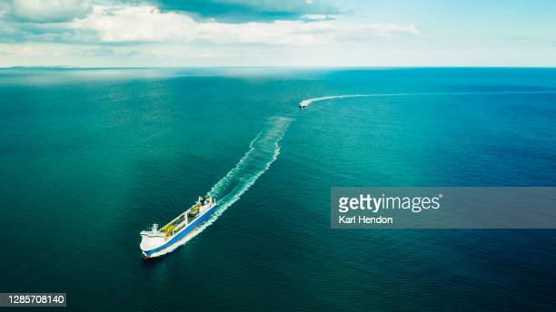 an aerial view of a container ship carrying cargo on the solent sea - environment stock pictures, royalty-free photos & images