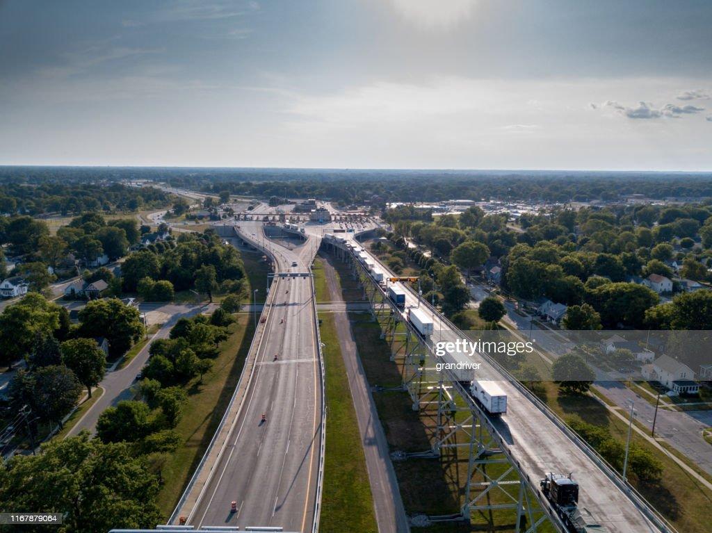 カナダ国境でアメリカに入るのを待っているセミトラックのラインの航空写真 : ストックフォト