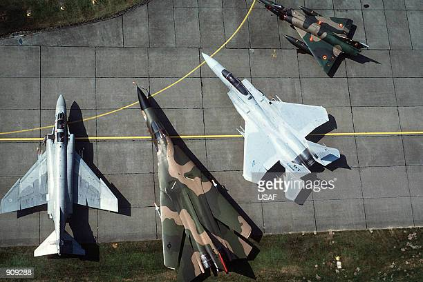 An aerial view of a multinational multiaircraft static display including left to right an F4 Phantom II an F111 an F15 Eagle and a French Mirage
