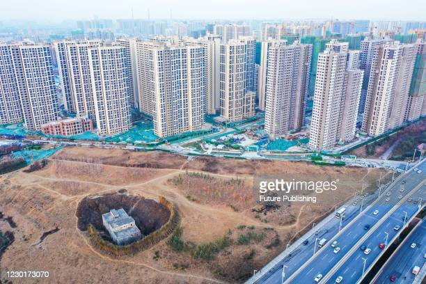 An aerial view of a 'nail house' trapped in a planned greenery area, a former village, in Zhengzhou city in central China's Henan province Tuesday,...