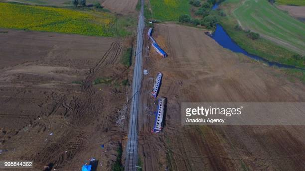 An aerial view of a passenger train on the repaired railway passing five derailed carriages, which await removal, after the accident at the Sarilar...