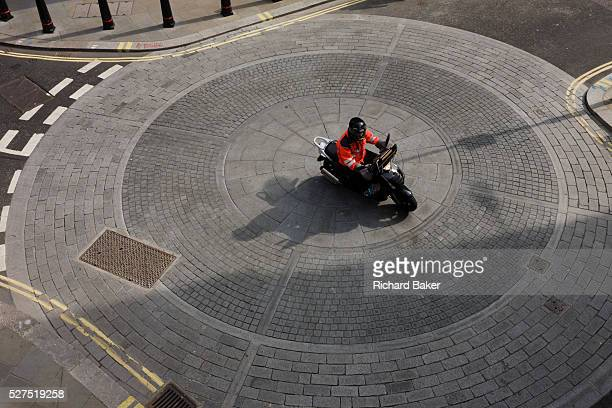An aerial view of a scooter bike rider as he crosses a circular mini roundabout in the City of London. Instead of circling the traffic junction...