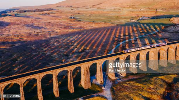 an aerial view of a train crossing ribblehead viaduct, north yorkshire - stock photo - public transport stock pictures, royalty-free photos & images