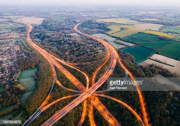 an aerial view of a uk motorway / freeway system at dawn - stock photo - motorway stock pictures, royalty-free photos & images