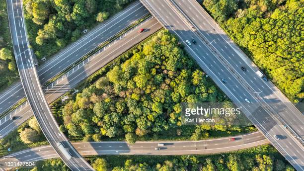 an aerial view of a uk motorway junction at sunset - stock photo - drone point of view stock pictures, royalty-free photos & images