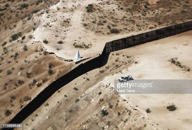 An aerial view of a US Border Patrol vehicle positioned next to the USMexico border barrier on June 28 2019 in Sunland Park New Mexico The obelisk is...