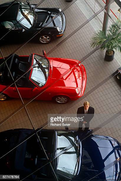 An aerial view of a west London Porsche car salesman in his salesroom We look down from a high vantage point to see three of his sports cars looking...