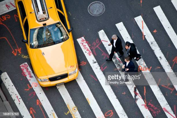 An aerial view of businessmen and taxis traversing a marked-up street in Midtown, NYC, June 2012. The street markings look like photo retouching...