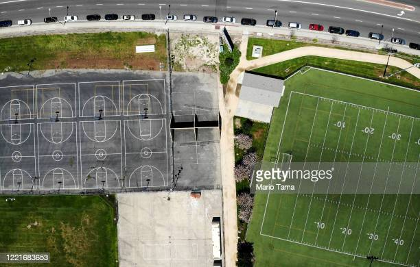 An aerial view of cars lined up to receive food distributed by the Los Angeles Regional Food Bank and the city as basketball courts and a football...