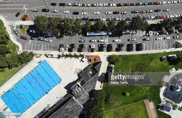 An aerial view of cars lined up to receive food distributed by the Los Angeles Regional Food Bank and the city near an empty community pool during a...