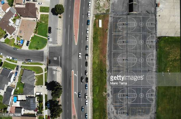 An aerial view of cars lined up to receive food distributed by the Los Angeles Regional Food Bank and the city as basketball courts stand empty at...