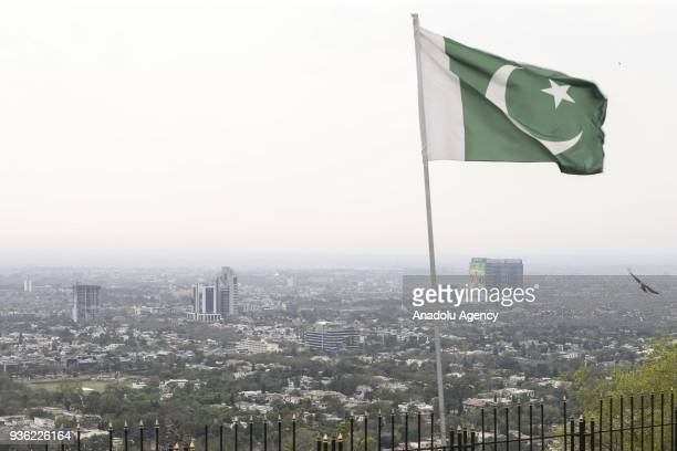 An aerial view of city scape is seen as a Pakistani flag is wawing in Islamabad Pakistan on March 14 2018 City staff prepared the city surroundings...