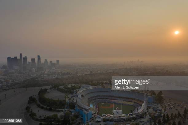 An aerial view of Dodger Stadium, downtown Los Angeles skyline and sunset is obscured by smoke, ash and smog Monday, Sept. 14, 2020 in Los Angeles....