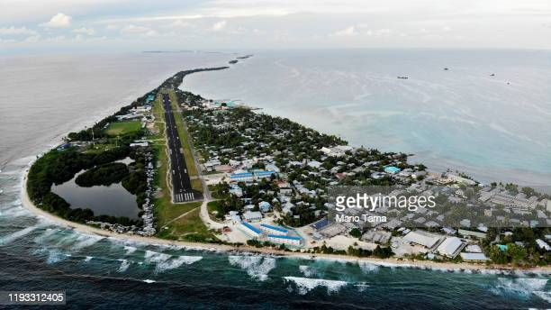 An aerial view of downtown and the airport runway between the Pacific Ocean and lagoon on November 28 2019 in Funafuti Tuvalu The lowlying South...