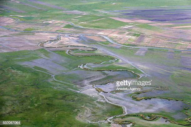 An aerial view of high peaks streams plains agricultural lands green areas roads neighborhoods and villages of Yuksekova and Semdinli districts in...