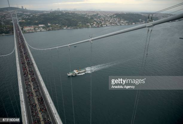 An aerial view of hundreds of participants competing as a boat passes Bosphorus during Vodafone 39th Istanbul Marathon at The 15 July Martyrs Bridge...