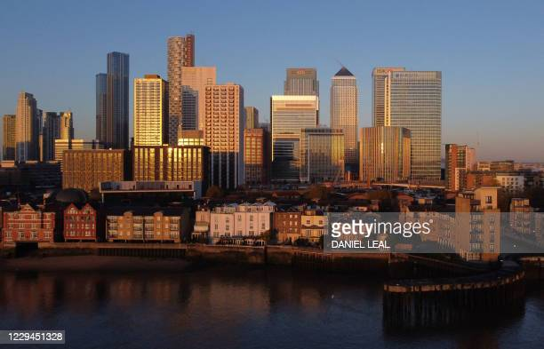 An aerial view of London's Canary Wharf financial district as the sun rises over the River Thames in London on November 4, 2020. - England heads into...