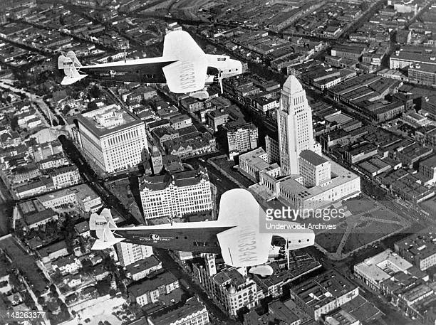An aerial view of Los Angeles with two Fokker monoplanes owned by Western Air Express flying over the recently completed City Hall Los Angeles...