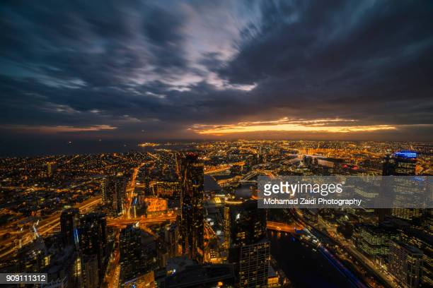 An aerial view of Melbourne cityscape including Yarra River and Victoria Harbour in the distance in long exposure.