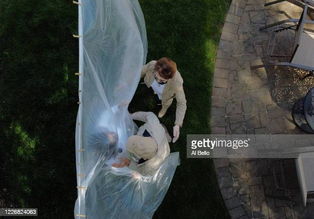 An aerial view of Michelle Grant hugging her father Domenick and Mary Grace Sileo through a plastic drop cloth hung up on a homemade clothes line...